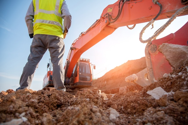 Engenheiro de construção usar equipamento de proteção pessoal ficar no local da estrada de construção