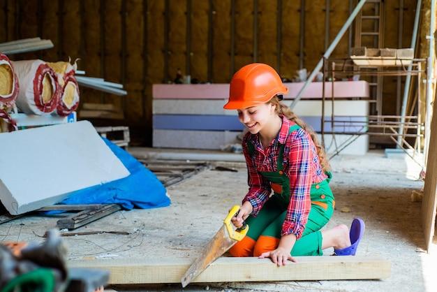 Engenheiro de criança feliz com uma ferramenta de martelo no capacete, reparando.