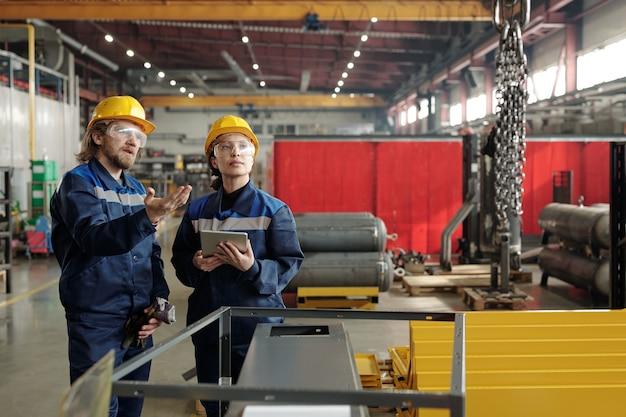 Engenheiro de fábrica barbudo com capacete e óculos de segurança apontando para correntes e explicando ao colega de trabalho como usar o guindaste industrial