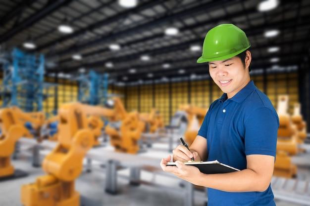 Engenheiro de fábrica está trabalhando com braço robótico na fábrica