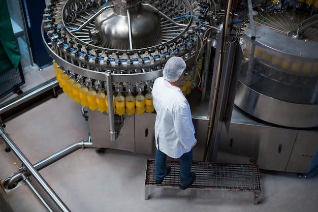 Engenheiro de fábrica, monitorando a garrafa de suco cheia na linha de produção