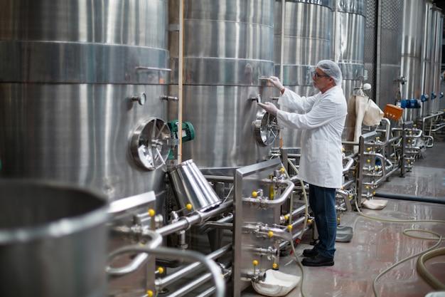 Engenheiro de fábrica monitorando um manômetro do tanque de armazenamento