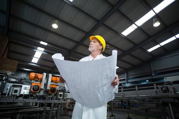 Engenheiro de fábrica pensativo segurando blueprint