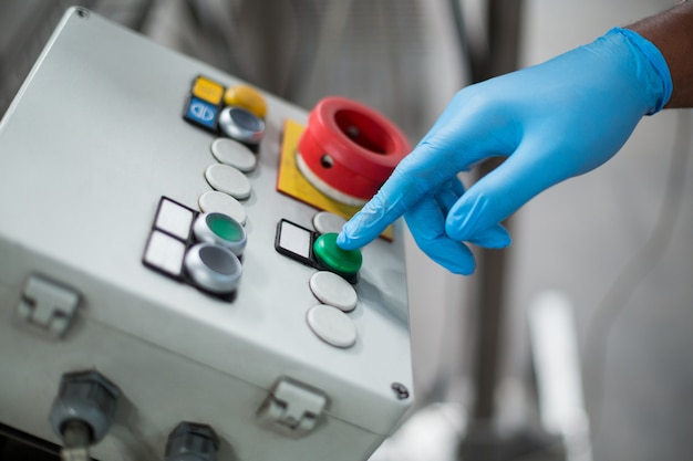 Engenheiro de fábrica, pressionando o botão na fábrica de garrafas