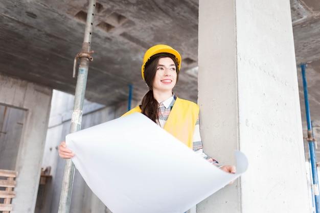 Engenheiro de garota no canteiro de obras com desenhos na mão