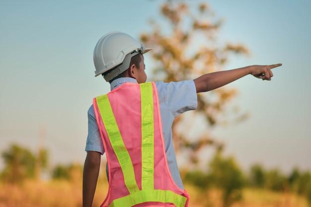 Engenheiro de garoto garoto permanente ao ar livre, segurando o conceito de sucesso de mão