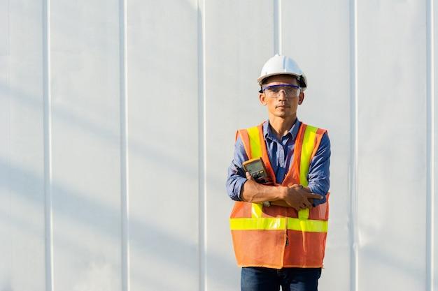 Engenheiro de homem bonito tailandês em pé com um medidor na frente do recipiente.
