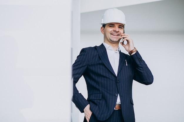 Engenheiro de homem de negócios bonito no capacete em um edifício