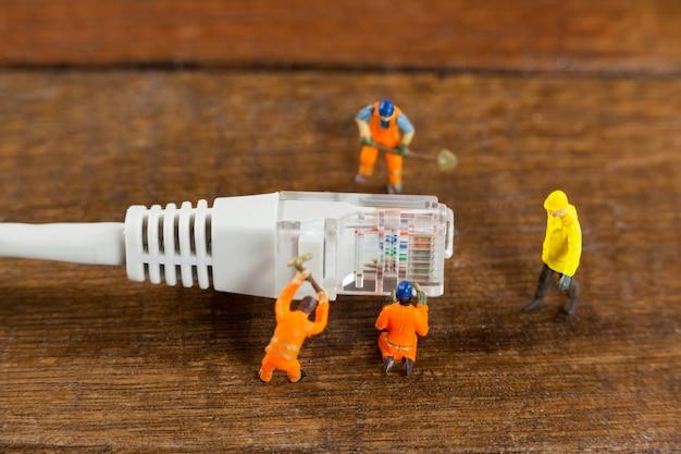 Engenheiro de miniatura e trabalhadores que trabalham com cabo lan