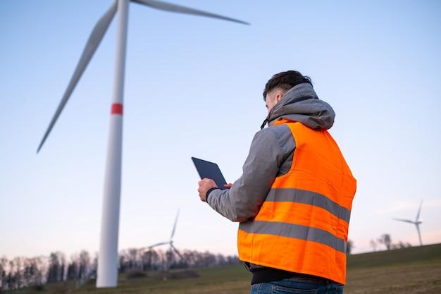 Engenheiro de moinho de vento faz manutenção e repara turbinas eólicas usando um tablet na vesta laranja