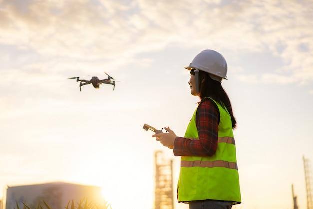 Engenheiro de mulher asiática operar drone voador sobre planta de refinaria de petróleo durante o nascer do sol