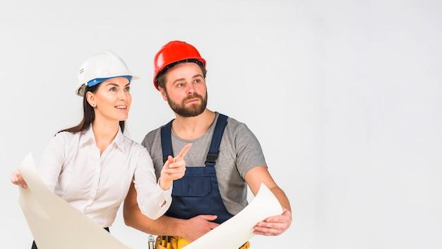 Engenheiro de mulher e construtor discutindo o projeto apontando para longe