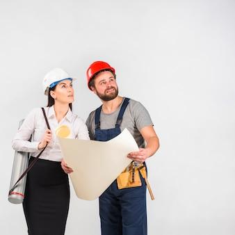 Engenheiro de mulher e construtor discutindo o projeto olhando para cima