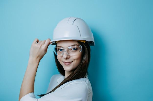 Engenheiro de mulher em capacete branco e óculos, roupas de proteção., capacete e óculos de proteção.
