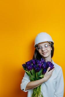 Engenheiro de mulher em óculos e capacete branco. cartaz de segurança. mulher de camisa branca detém grande monte de tulipas roxas.
