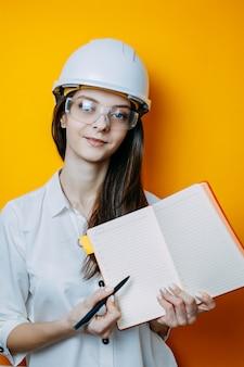 Engenheiro de mulher em óculos e capacete branco. cartaz de segurança. mulher de capacete possui caderno e caneta.