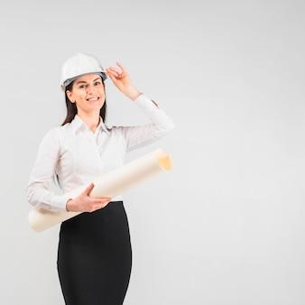 Engenheiro de mulher no capacete com rolo de papel whatman