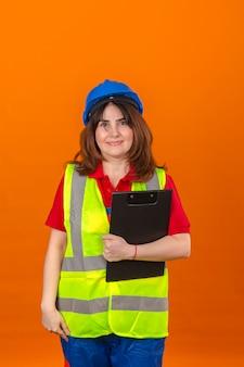 Engenheiro de mulher no colete de construção e capacete de segurança segurando a área de transferência nas mãos, olhando confiante com sorriso no rosto em pé sobre a parede laranja isolada