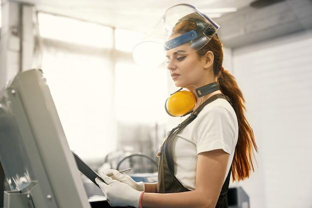 Engenheiro de mulher trabalhando na fábrica com máquina computadorizada.