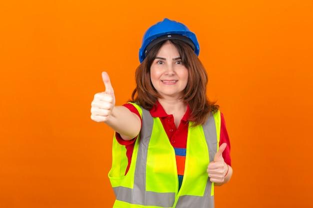 Engenheiro de mulher usando colete de construção e capacete de segurança com sorriso no rosto, aparecendo os polegares sobre parede laranja isolada