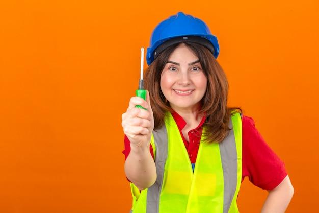 Engenheiro de mulher usando colete de construção e capacete de segurança em pé com chave de fenda sorrindo amigável sobre parede laranja isolada