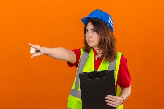 Engenheiro de mulher usando colete de construção e capacete de segurança segurando a área de transferência e apontando para algo com cara séria sobre parede laranja isolada
