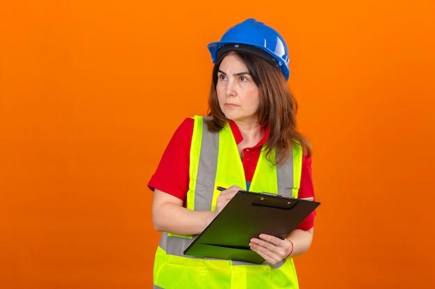 Engenheiro de mulher usando colete de construção e capacete de segurança segurando a prancheta fazendo anotações com cara séria, olhando de lado por cima isolado parede laranja