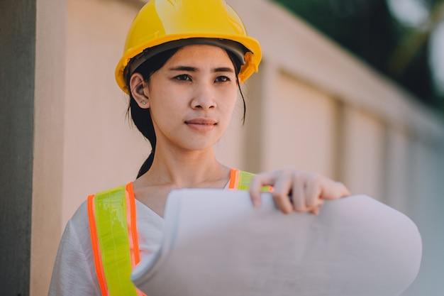 Engenheiro de mulheres asiáticas segurando o canteiro de obras de trabalho