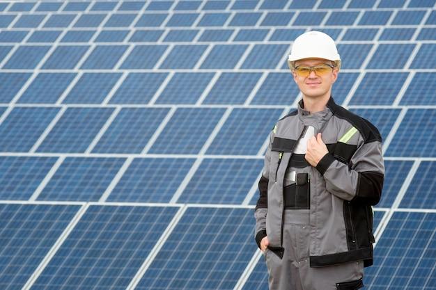 Engenheiro de painéis solares em barril branco, óculos de proteção amarelos e roupa cinza em pé perto do campo de painéis solares. conceito de energia renovável e limpa, tecnologia. copie o espaço. homem a trabalhar.