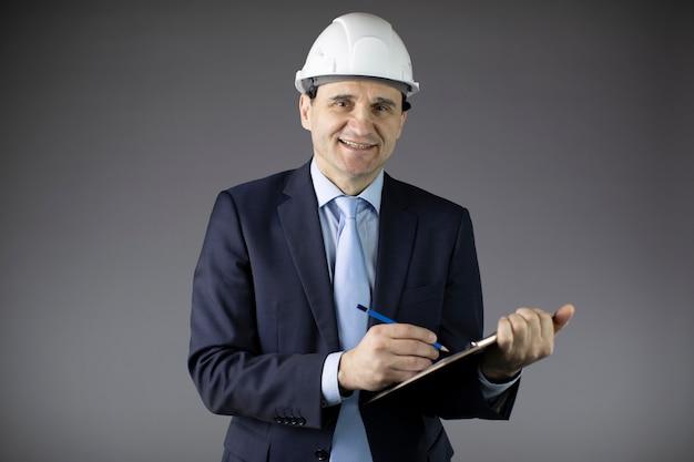 Engenheiro de petróleo no capacete faz anotações na área de transferência e olha para a câmera com um sorriso