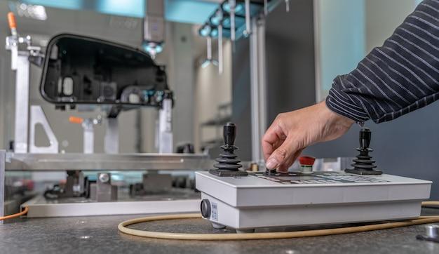 Engenheiro de qualidade controla um instrumento para medição 3d de peças fundidas de plástico na indústria automotiva