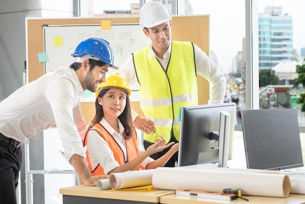 Engenheiro de raça mista homem caucasiano e mulher asiática usar capacete discutindo sobre o plano de construção