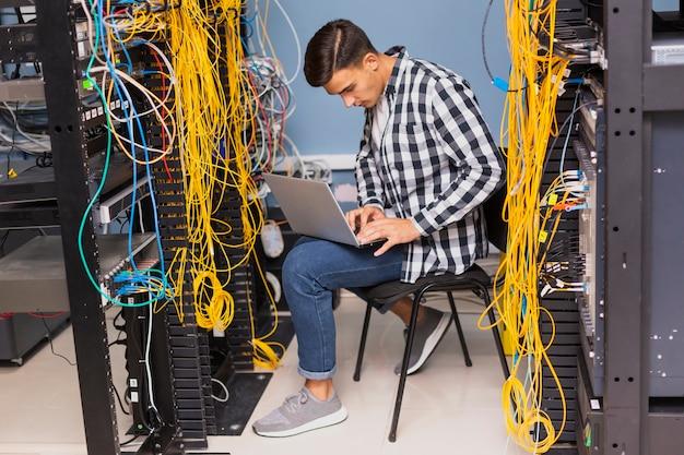 Engenheiro de rede com um laptop tiro no escuro