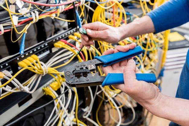 Engenheiro de rede trabalhando na sala do servidor. conexão de cabos de rede a comutadores