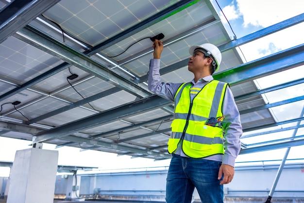 Engenheiro de serviço e manutenção para sistema de telhado solar verificando o desempenho energético da célula solar