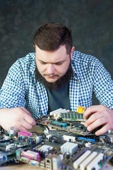 Engenheiro de serviço trabalha com placa-mãe de computador quebrada. tecnologia de reparo de componentes eletrônicos