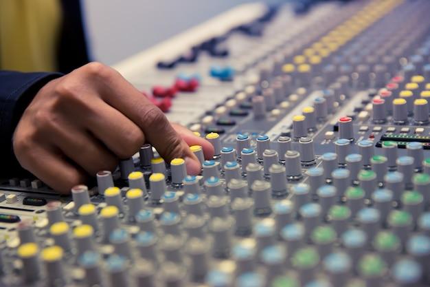Engenheiro de som ajustar o volume no mixer de som