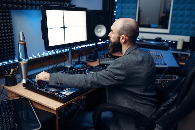 Engenheiro de som olhando para o monitor no painel de controle remoto no estúdio de gravação.