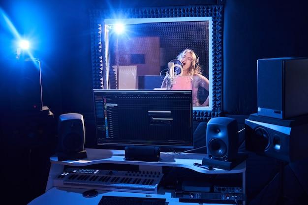 Engenheiro de som profissional masculino, mixando áudio em estúdio de gravação. tecnologia de produção musical, garota cantando no microfone