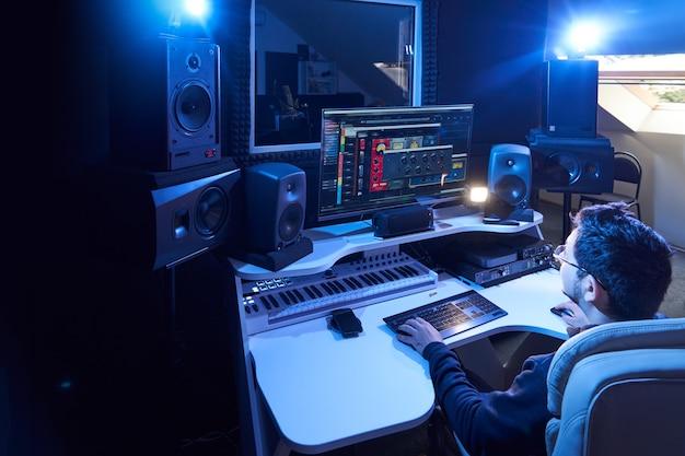 Engenheiro de som profissional masculino, mixando áudio em estúdio de gravação. tecnologia de produção musical, trabalhando no mixer