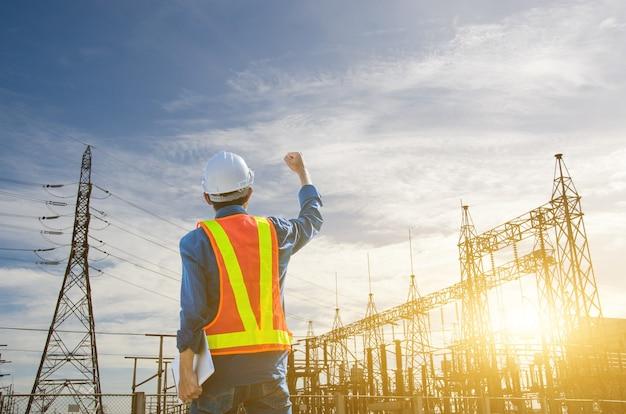 Engenheiro de sucesso em pé na subestação de energia contra o fundo do nascer do sol