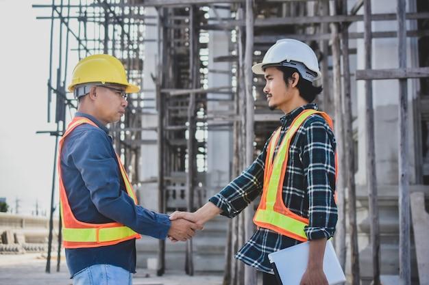 Engenheiro de trabalho em equipe aperta a mão no fundo de construção do local