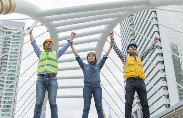 Engenheiro de trabalho em equipe asiáticos em pé e mãos levantadas
