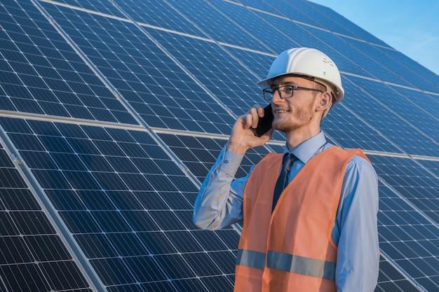 Engenheiro de uniforme em pé sobre um fundo de painéis solares a fazenda solar falando ao telefone