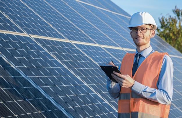 Engenheiro de uniforme em pé sobre um fundo de painéis solares. a fazenda solar verifica o funcionamento do sistema, energia alternativa para conservar a energia mundial, idéia de módulo fotovoltaico para limpeza