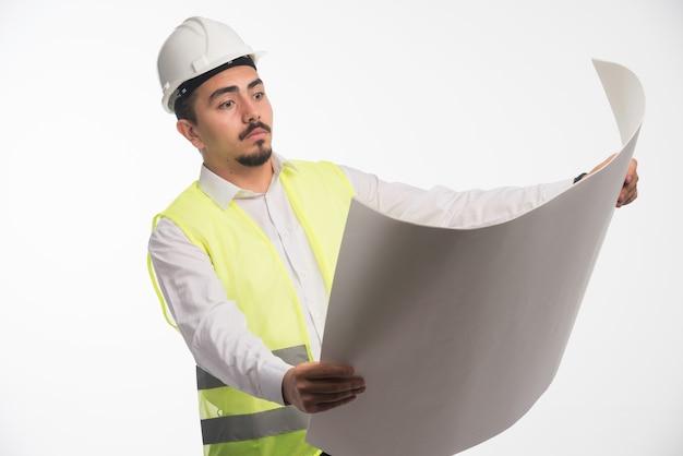 Engenheiro de uniforme segurando e lendo a planta arquitetônica da construção.