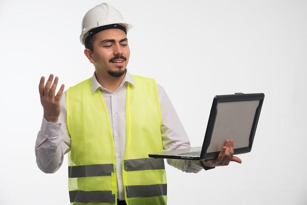 Engenheiro de uniforme segurando um laptop e falando.
