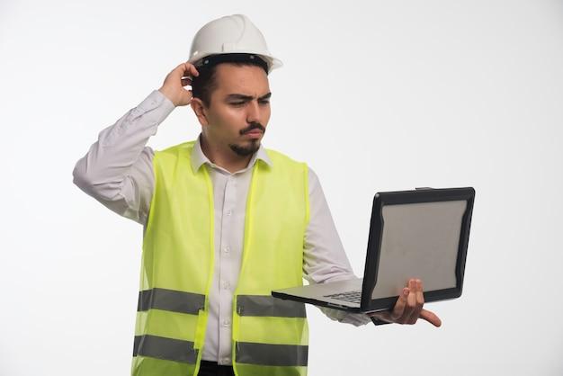 Engenheiro de uniforme segurando um laptop e tendo uma reunião online.