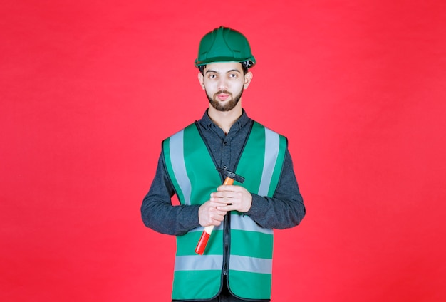 Engenheiro de uniforme verde e capacete segurando um machado de madeira.