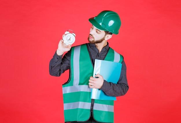 Engenheiro de uniforme verde e capacete segurando uma pasta azul e um despertador.